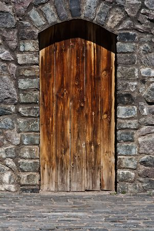 Old, wooden door in a wall from a large stone photo