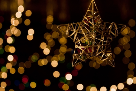 Christmas gold star against background of blurred lights Stock Photo - 6037387