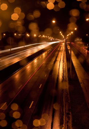 A night time shot of speeding traffic on a road photo