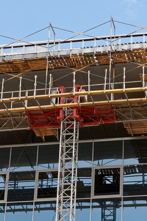 Modern buildings under construction. Metal scaffolding with wooden planks. photo