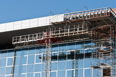 Reflection of building designs in windows of an under construction building photo
