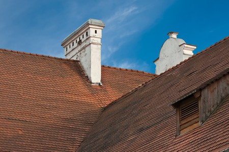 Hight red tiled roof with chimney and dormer window photo