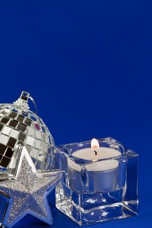 Burning candle and Christmas decoration on blue background photo