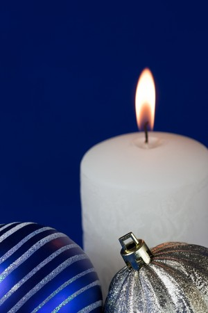 Christmas candle & wintery decorations on a dark blue background photo