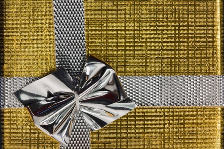 Christmas golden gift box wrap and silver bow photo