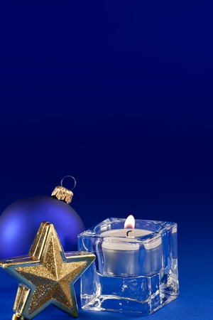 Burning candle and Christmas star on blue background photo