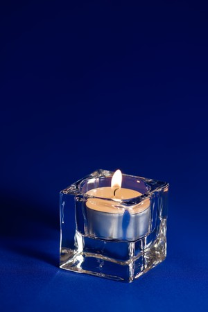 Burning candle in a glass candlestick on a dark blue background photo