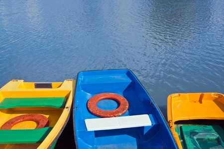 landing stage: Small blue and yellow row boats moored at landing stage