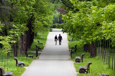 Young couple walking in the summer park photo