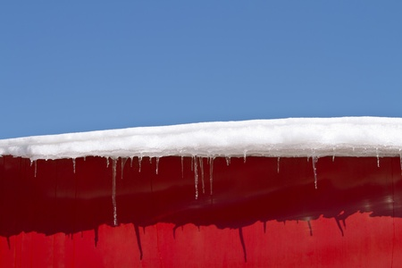 Snow covered roof with icicles photo