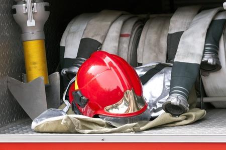 赤い消防士のヘルメットおよびホース 写真素材
