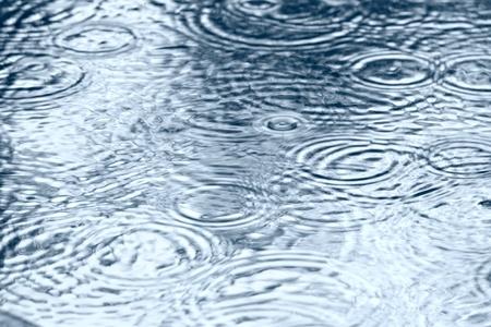 circulos concentricos: La superficie del agua con gotas de lluvia cayendo Foto de archivo
