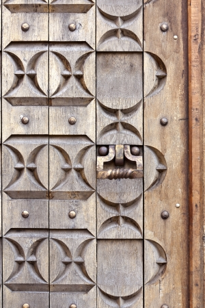 Old ornate wooden door with knocker photo