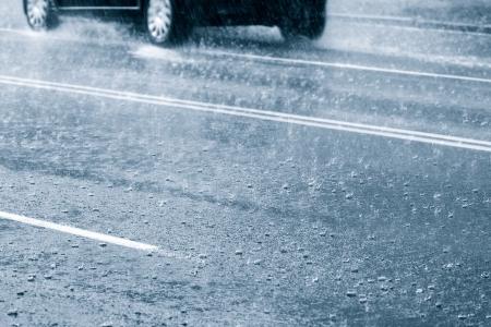 downpour: Car driving through a large puddle in a downpour