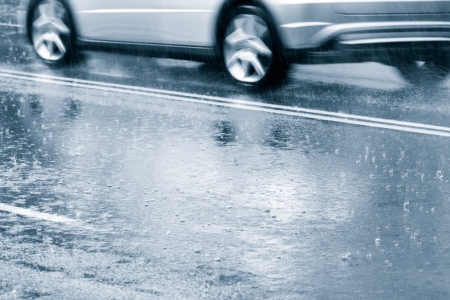 Car driving through a large puddle in a downpour photo