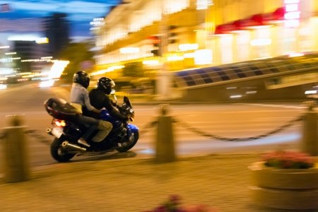 Man and woman on motorcycle at night city photo