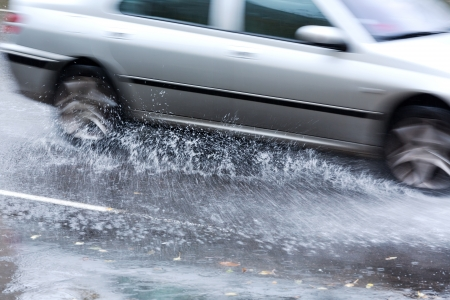torrential: Car splashes through a large puddle on a wet road Stock Photo