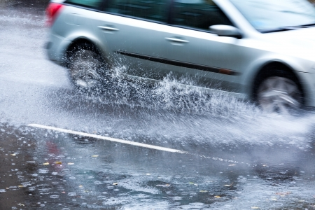 rain wet: Car driving through a large puddle in a downpour
