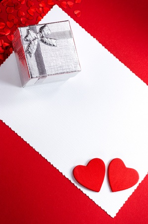 Little silver gift box on red background photo