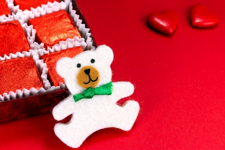 valentine s day teddy bear: Cute teddy bear with candy and two red hearts