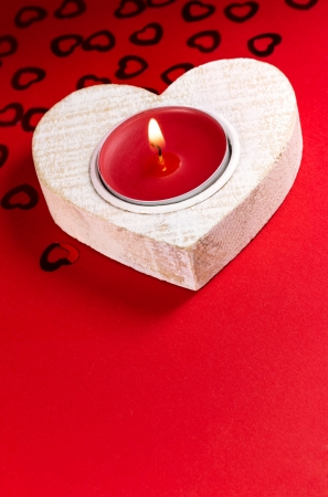 Burning candle on wooden heart candlestick photo