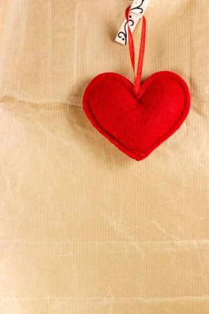 Red heart over brown paper gift bag photo