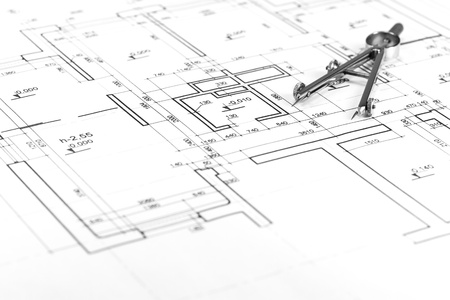Drawing compass on architectural blueprints