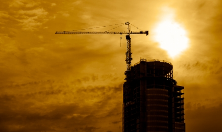 Building construction at sunset with tower crane photo