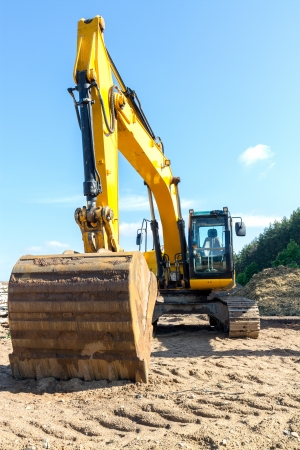 Yellow excavator on a construction site photo