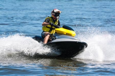 ジェット スキーに乗る男ウェット パーソナルウォーター クラフトのバイク 写真素材