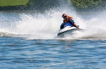 Men riding wave runner on river