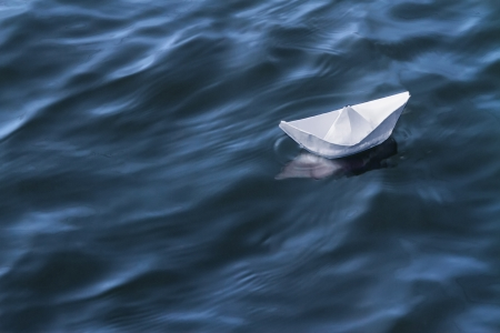 White paper boat on blue water photo