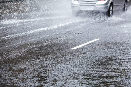 Car driving in the city street after heavy rain