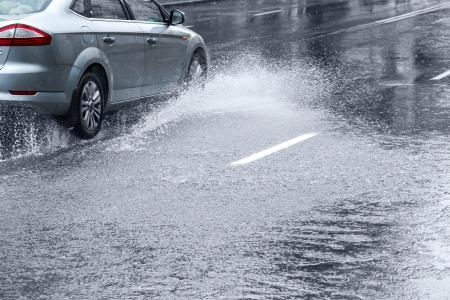 車の巨大な水たまりに豪雨時運転 写真素材
