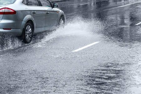 Car driving on huge puddle during a downpour Stok Fotoğraf