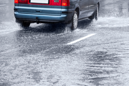Car splashes through a puddle on a wet road photo