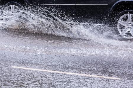 濡れた路面で大きな水たまりをはねかける車