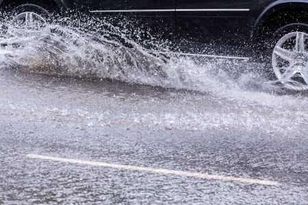 Car splashes through a large puddle on a wet road Stok Fotoğraf