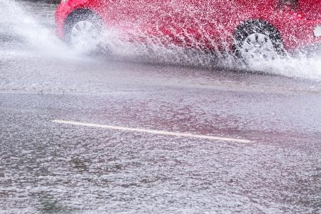 Splash by a car as it goes through flood water photo