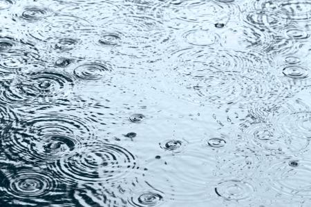 空の反射と水たまりで波立つ雨の滴