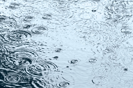 Rain drops rippling in a puddle with sky reflection Standard-Bild