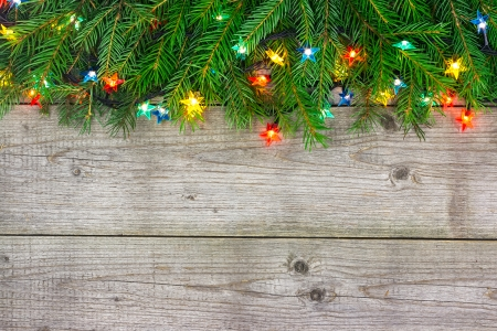 Fir tree branch decorations with garlands of lights on wooden  photo