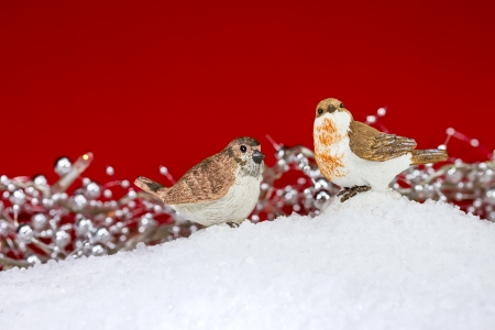 Two cute Christmas birds figurine on red  photo