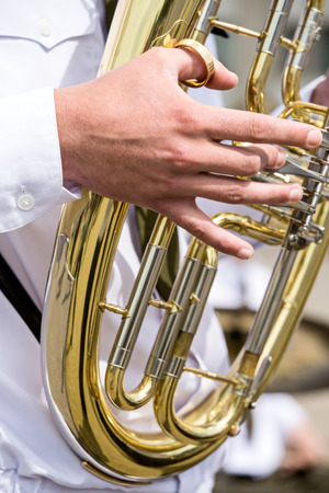 Closeup of copper tuba in hands of musician photo