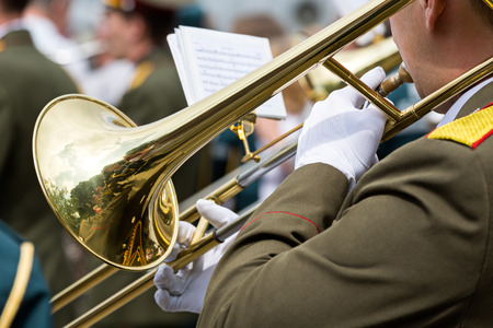 Military musicians blowing gold trombones photo
