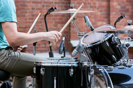 若いドラマー ドラム セットで遊んで