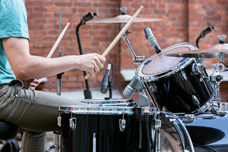 Young drummer playing at drums set photo