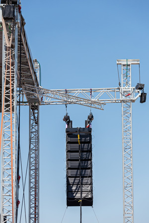 Professional sound equipment high above an outdoor concert photo