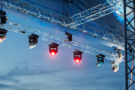 Professional lighting equipment high above an outdoor concert