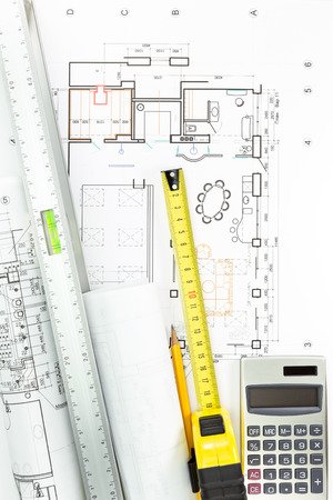 Construction building plans with calculator, pencil, spirit level and tape measure